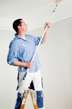 House painter on step ladder painting a ceiling with a roller on a pole.